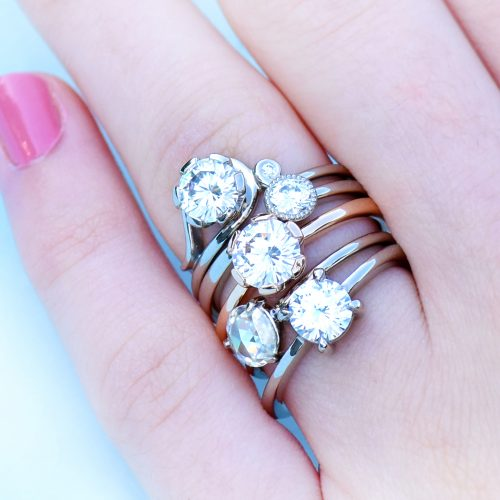 Five of Lilia Nash's moissanite engagement rings. Top to bottom: Art Nouveau, Petite Solitaire, Signature Solitaire with flower setting, Rose Cut Solitaire & custom solitaire.