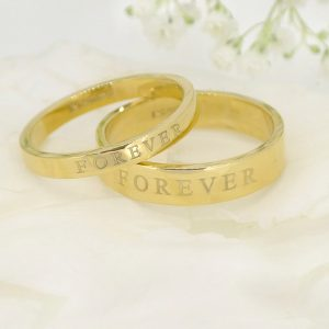 Bespoke matching wedding rings by Lilia Nash. 18ct gold wedding bands engraved with 'FOREVER'.