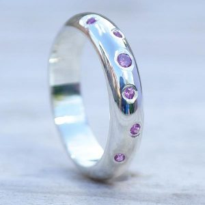 Bespoke wedding rings by Lilia Nash. 18ct white gold purple sapphire scattered wedding band.