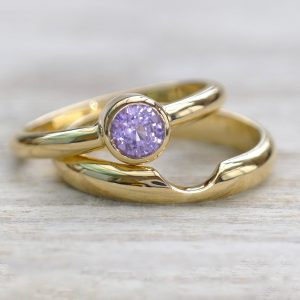 A fair trade purple sapphire solitaire engagement ring and matching stacking wedding ring in 18ct gold.