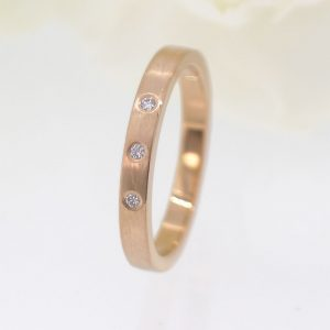 Bespoke wedding rings by Lilia Nash. This custom design is 18ct rose gold set with fair trade diamonds.