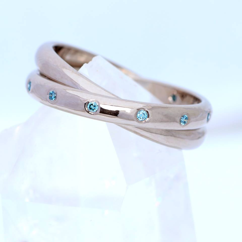 A custom designed wedding ring by Lilia Nash. 18ct white gold rolling ring set with ethical blue diamonds.