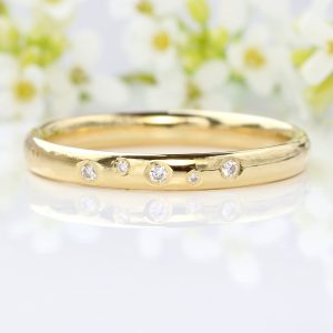 An 18ct gold wedding ring set with a scattering of fair trade Canadian white diamonds. Handmade wedding rings by Lilia Nash.