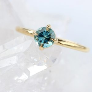 A 5mm 0.7 carat fair trade Montana blue-teal sapphire is held in a 4 prong setting, which gives maximum views of the beautiful stone from all angles. As the setting sits proud on top of the 18ct gold 1.5mm halo band, a wedding band or a stacking ring will sit flush against the ring.