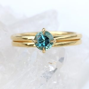 Fair trade Montana blue-teal sapphire is held in a 4 prong setting. Shown with a matching wedding band.
