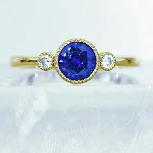 Lilia Nash - Ethical designer jewellery. Signature trilogy ring in 18ct gold set with a 6mm blue sapphire & moissanites.