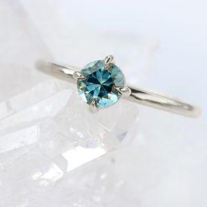Handmade ethical designer jewellery by Lilia Nash - 18ct white gold engagement ring with a blue-teal Montana sapphire.