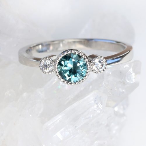solid 950 platinum ring, set with a fair trade Montana teal-blue sapphire and side diamonds. Available in size M 1/2, but can be adjusted