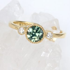 An ethical trilogy engagement ring, set with a fair trade Australian green teal sapphire, flanked by two ethical Canadian diamonds. The ring is make from recycled 18ct gold. Available in size M but can be resized.