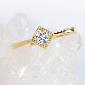 Unusual engagement ring featuring a Princess cut moissanite gem. The ring can be made from 18ct golds or platinum.