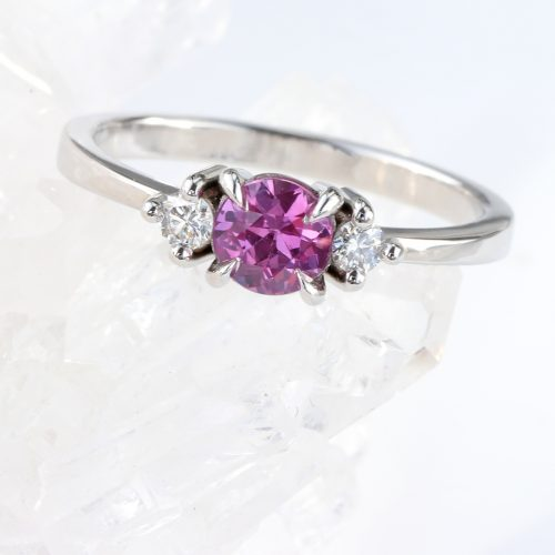 A one of a kind platinum engagement ring in a trilogy design with two fair trade diamonds and a dazzling natural pink sapphire.