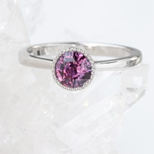 A unique pink to purple colour change sapphire engagement ring in solid 950 platinum. Ethical jewellery design by Lilia Nash.